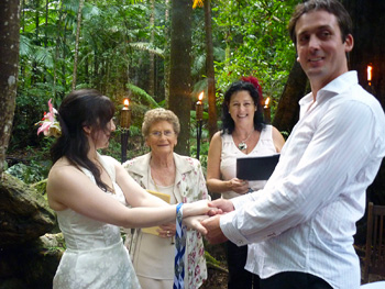 Damian's Grandmother draps the Blue Cord over Damian & Clare's Hands in the Handfasting with Marry Me Marilyn at Crystal Creek Rainforest Retreat in NSW