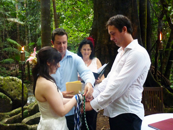 Damian's Brother draps the Green cord over Damian & Clare's Hands in the Handfasting with Marry Me Marilyn at Crystal Creek Rainforest Retreat in NSW
