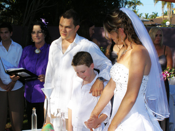 Melinda David & Riley pouring sand into the central vase from their separate bottles of coloured sand in their Sand Ceremony at their Mermaid Waters home on the Gold Coast with Marry Me Marilyn